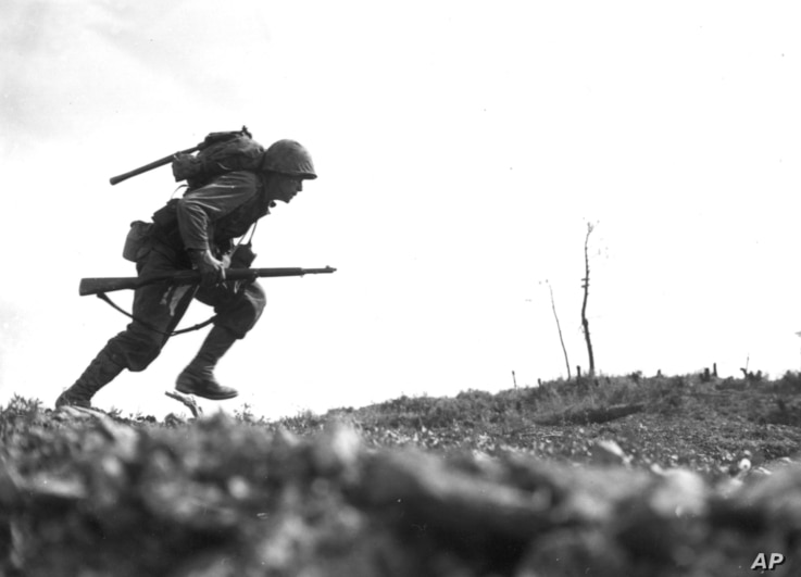 Pfc. Paul Ison from the 6th Marine Division dashes forward through Japanese machine-gun fire while crossing a draw on Okinawa, May 10, 1945.