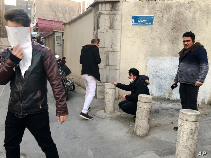 In this photo taken by an individual not employed by the Associated Press and obtained by the AP outside of Iran, people are affected by tear gas fired by anti-riot Iranian police to disperse demonstrators in a protest over Iran's weak economy, in Te...
