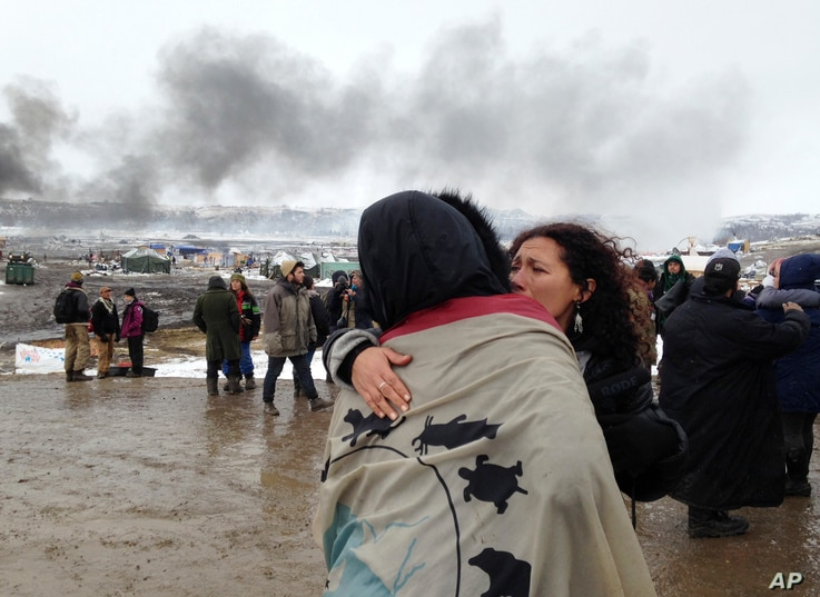 A couple embraces as opponents of the Dakota Access pipeline leave their main protest camp, Feb. 22, 2017, near Cannon Ball, N.D., as authorities were preparing to shut down the camp in advance of spring flooding season. The Army Corps of Engineers o...