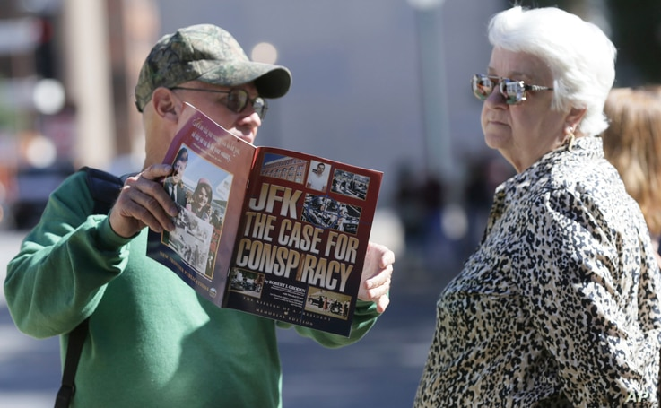 A vender shows Marie Ross of Pennsylvania a magazine during her visit to Dealey Plaza Dallas, Wednesday, Oct. 25, 2017.