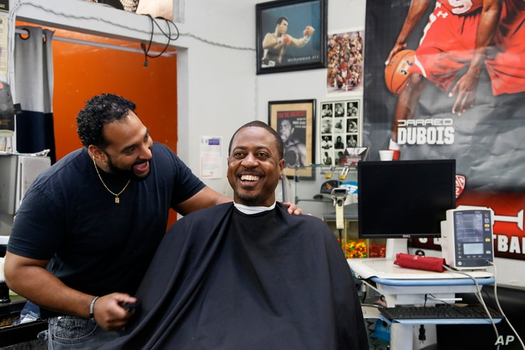 Barber Eric Muhammad, owner of A New You Barbershop, left, jokes with regular customer Marc M. Sims before measuring his blood pressure in Inglewood, California, March 11, 2018.