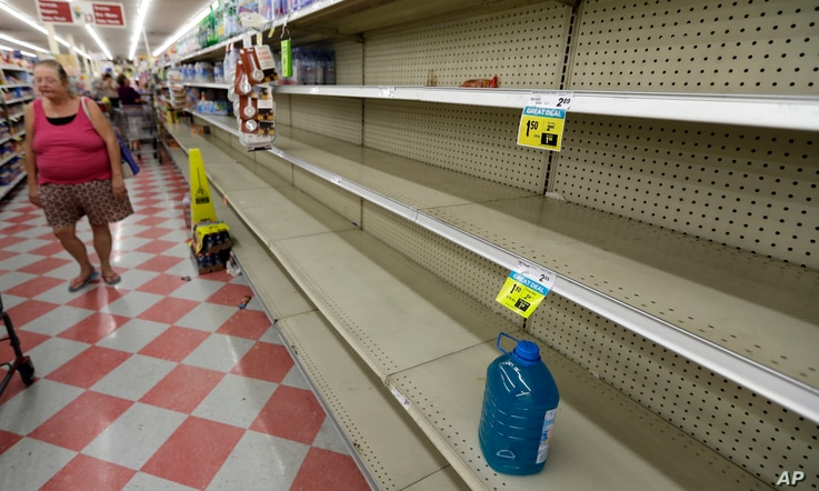 Shoppers pass empty shelves along the bottled water aisle in a Houston grocery store as Hurricane Harvey intensifies in the Gulf of Mexico, Aug. 24, 2017.