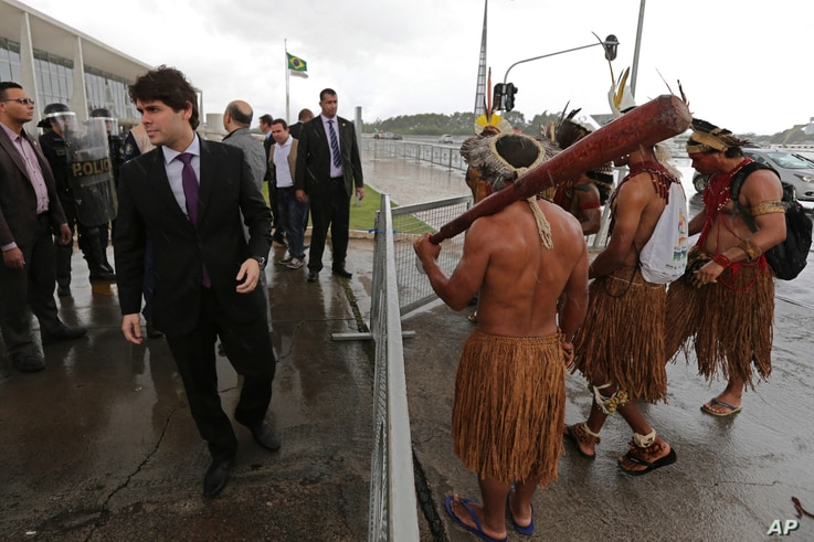 FILE - Security officials block Pataxo indigenous men from entering the Planalto presidential palace in Brasilia, Brazil, Nov. 22, 2016. Brazil's various indigenous groups were demanding that the government recognize their ancestral lands and provide...