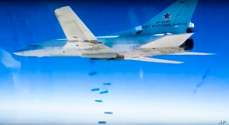 FILE - Russian  Tu-22M3 bomber drops bombs on a target in photo made from video footage provided by the Russian Defense Ministry, Dec. 9, 2015.