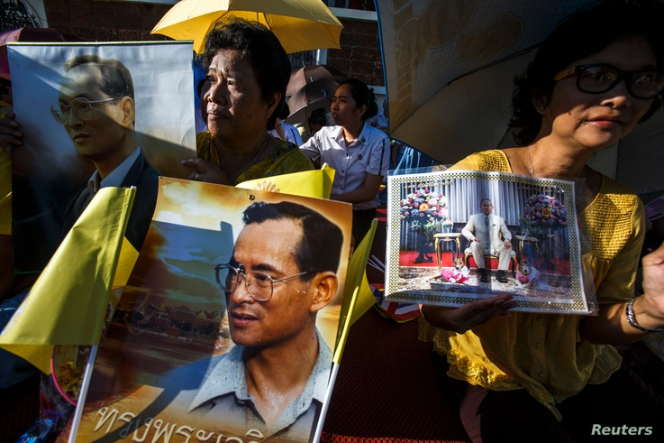 Well wishers hold a picture of Thailand's King Bhumibol Adulyadej as they gather with others outside the palace where he is staying in Hua Hin, Prachuap Khiri Khan province, during Coronation Day, May 5, 2014.