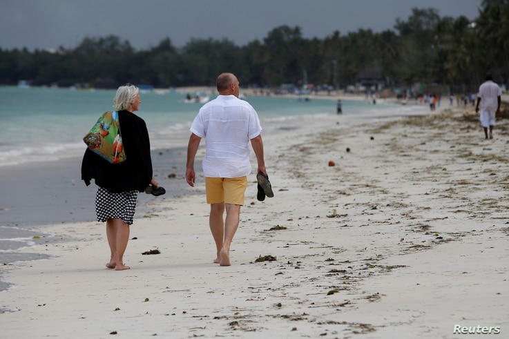 Tourists walk on a beach in Mombasa, Kenya, Aug. 5, 2017.
