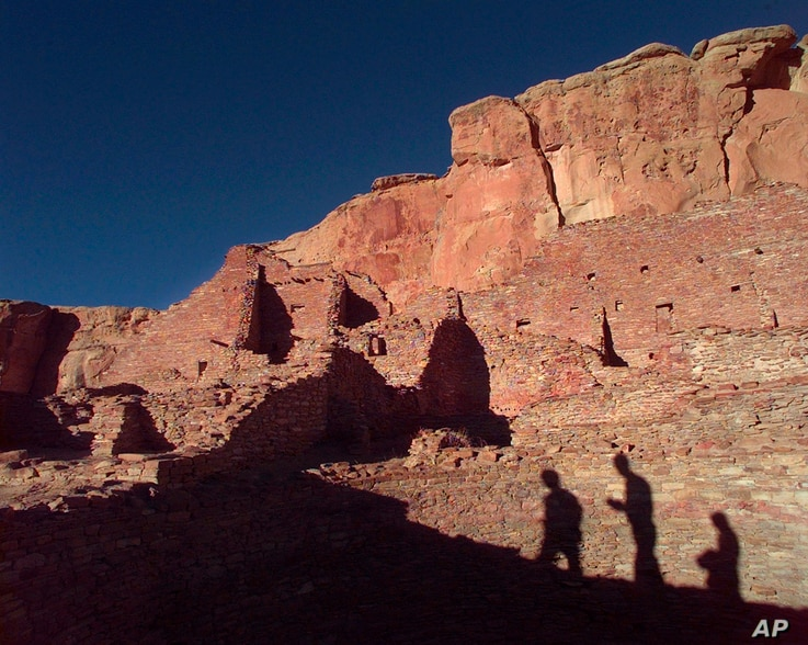 FILE - Tourists cast their shadows on the ancient Anasazi ruins of Chaco Canyon in New Mexico, Nov. 21, 1996. Research suggests three archaeological sites in the Southwest: Chaco Canyon, Aztec Ruins and Casas Grandes represent three successive stages...