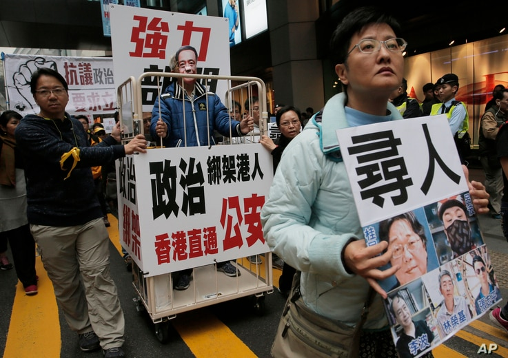 FILE - A protester wearing a mask of bookseller Lee Bo stands in a cage during a protest against the disappearances of booksellers in Hong Kong, Jan. 10, 2016.