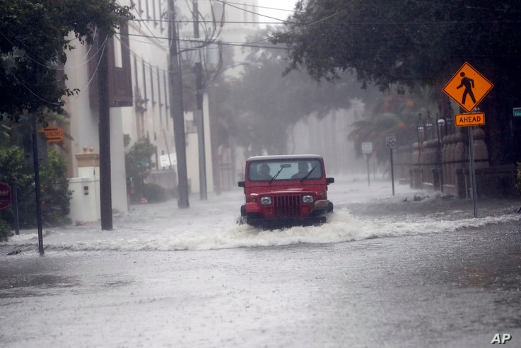 A motorist drives down flooded street in St. Augustine, Fla., as  Hurricane Matthew moves up the Florida coast Oct. 7, 2016.