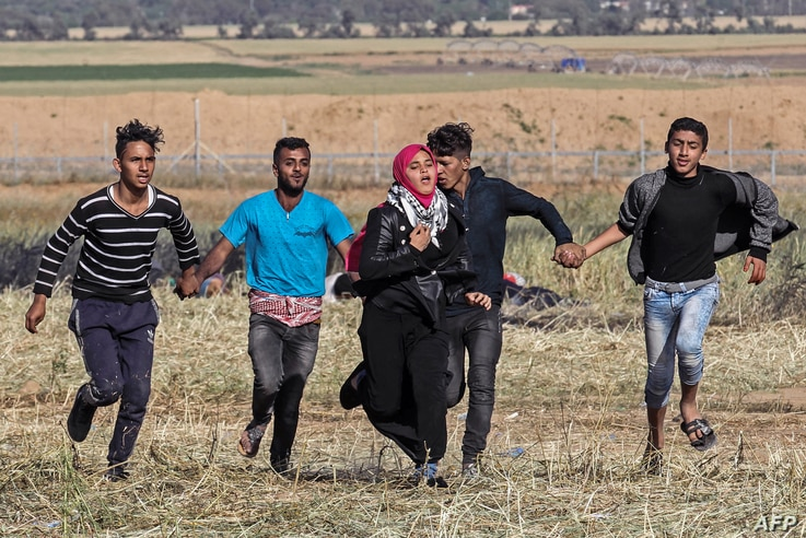 Palestinian protesters hold hands to protect a girl from shots as they run for cover during clashes with Israeli security forces following a demonstration near the border with Israel, east of Khan Yunis, in the southern Gaza Strip on March 31, 2018.