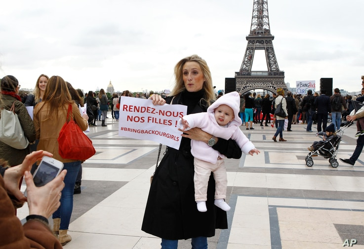 """A woman holds her baby and a poster reading """"Bring Back our Girls"""" during a rally to support the release of the kidnapped Nigerian girls at the Trocadero, in front of the Eiffel Tower, in Paris on May 13, 2014."""