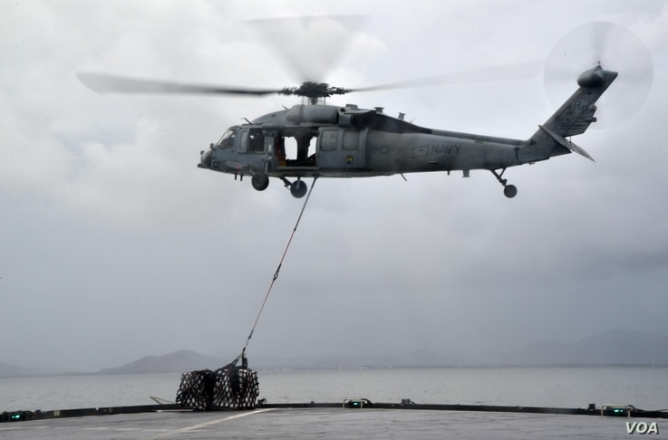 "A MH-60S helicopter, from the ""Island Knights"" of Helicopter Sea Combat Squadron (HSC) 25, from the Military Sealift Command dry cargo and ammunition ship USNS Charles Drew (T AKE 10), transports a pallet of water en route to the Republic of the ..."