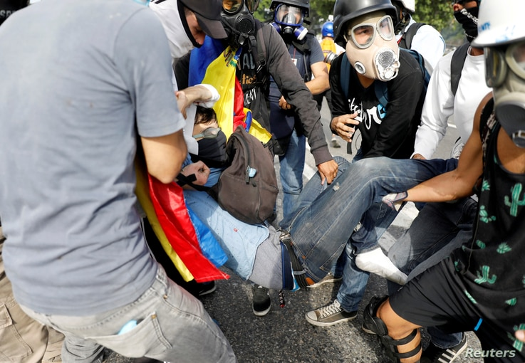 David Jose Vallenilla (C), who was fatally injured, is helped by fellow protesters outside an air force base during clashes with riot security forces at a rally against Venezuelan President Nicolas Maduro's government in Caracas, June 22, 2017.