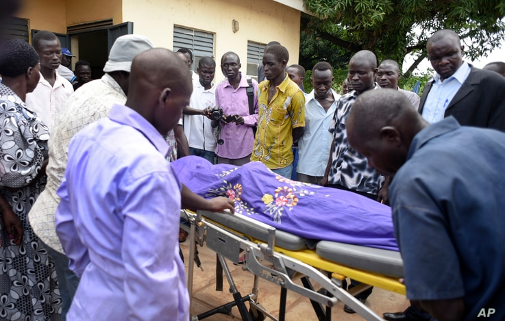 Relatives and onlookers watch as the body of South Sudanese journalist Peter Moi is taken into a mortuary in Juba, South Sudan, Aug. 20, 2015.