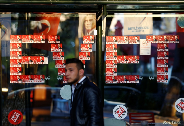 """""""Yes"""" stickers with pictures of Turkish President Recep Tayyip Erdogan are placed at a bus stop, in Istanbul, Turkey, April 14, 2017."""