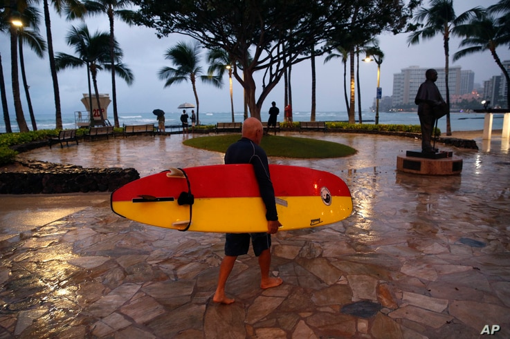 A surfer walks along Waikiki Beach in a light rain from Tropical Storm Lane, Aug. 25, 2018, in Honolulu.