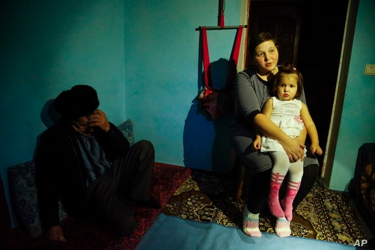 FILE - Elnara, the wife of arrested Tatar protester Ali Asanov, is seen with one of her daughters in their home in Urozhayne, Crimea, Jan. 24, 2016. Russian authorities have used arrests as part of an intimidation campaign against local Tatars, right...
