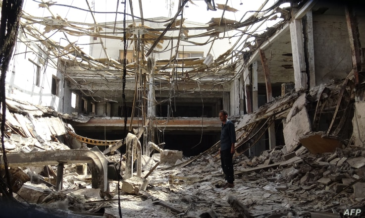 A man stands amidst the rubble on Dec. 17, 2018, at a factory damaged during fighting and air strikes.