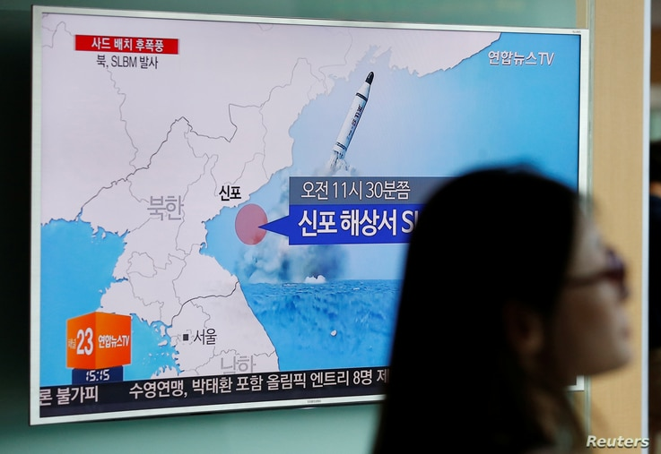 A passenger walks past a TV screen at a railway station in Seoul, South Korea, broadcasting a news report on North Korea's submarine-launched ballistic missile fired from North Korea's east coast port of Sinpo July 9, 2016.   REUTERS/Kim Hong-Ji