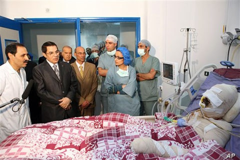 In this photo released 28 Dec 2010 by the Tunisian President's office, Tunisia's President Zine El Abidine Ben Ali, 2nd left, visits Mohamed Bouazizi, a young man who set himself on fire after police confiscated fruit and vegetables he sold without a...