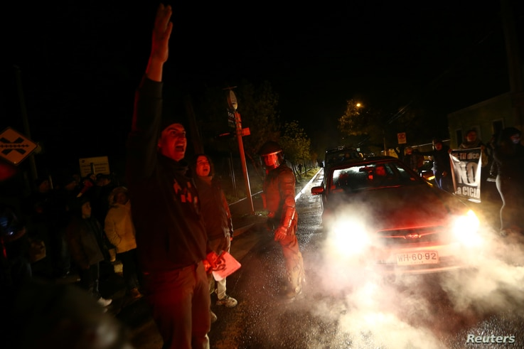 Locals shout slogans as they attempt to block a mountain road during a protest against a new industrial waste processing facility that is being constructed in Til Til, Chile, Aug. 11, 2017.