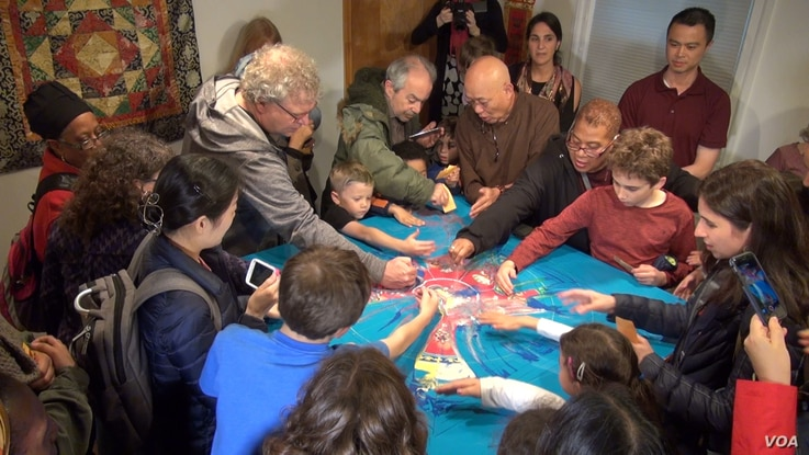People of all ages are dismantling the sand mandala that is an integral part of the ancient ritual art. (VOA/ J. Soh)