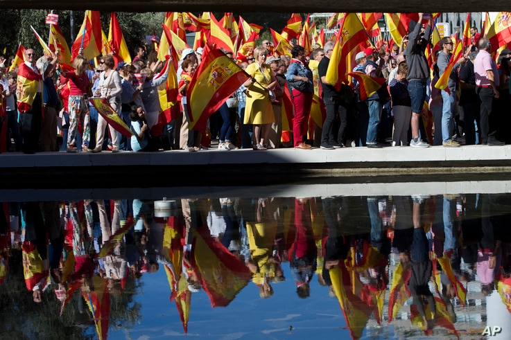 Spaniards pack Colon Square in Madrid, Spain, Saturday, Oct. 7, 2017. Thousands of pro-Spanish unity supporters donning Spanish flags have rallied in a central Madrid plaza to protest the Catalan regional government's drive to separate from Spain.