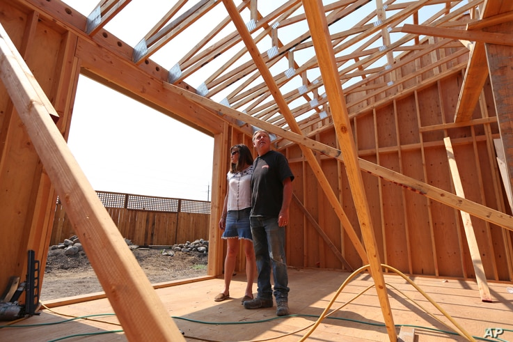 In this Aug. 9, 2018 photo, Cheri and Paul Sharp stand among the wooden beams framing their future home in Santa Rosa, Calif.