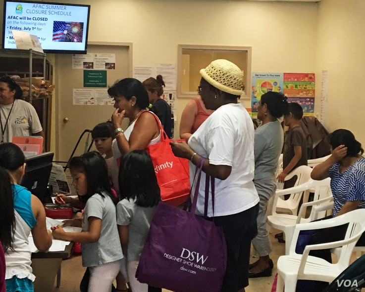 Low income residents line up to receive free groceries at the Arlington Food Assistance Center in Arlington, Va. on June 28, 10`6. (VOA/CMaddux)