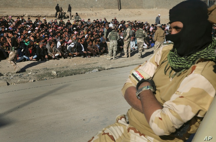 A face covered Iraqi soldier sits on his humvee in front of scores of Iraqi male residents who were rounded up by Iraqi forces, in Gogjali neighborhood, in Mosul, Iraq, Nov. 24, 2016. Iraqi forces urged them to come out with information of any Islami...