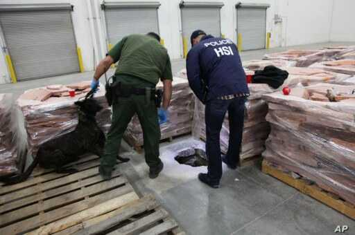 Investigators looking at the entrance to a drug-smuggling tunnel in a warehouse in Otay Mesa in southern California. Nov. 15, 2011