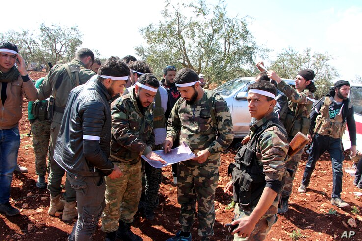 Turkey-backed Free Syrian Army fighters advance in Der Mismis village in the southeast portion of Afrin, Syria, March 13, 2018. Turkish troops and allied Syrian opposition fighters have intensified attacks on the Syrian Kurdish-held town of Afrin.