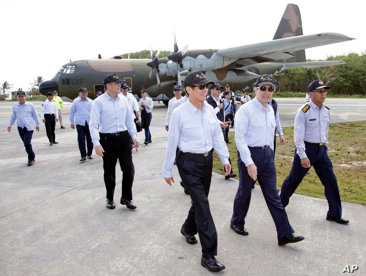 Jan. 28, 2016 file photo released by the Taiwan Presidential Office, Taiwan's President Ma Ying-jeou, second from right, arrives on his visit to the Taiping Island, also known as Itu Aba, in the Spratly archipelago, in the South China Sea.