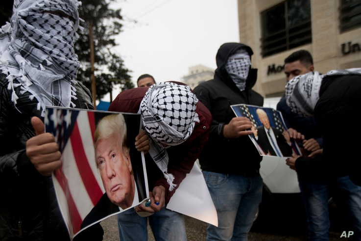 Palestinians holds posters of the U.S. President Donald Trump during a protest in the West Bank City of Ramallah, Dec. 6, 2017.