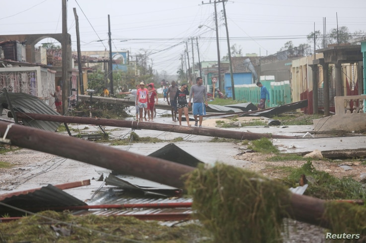 People walk on a damaged street after the passage of Hurricane Irma in Caibarien, Cuba, Sept. 9, 2017.