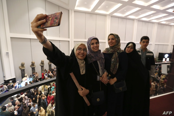 Theatre-goers take a selfie picture at the Espinas Hotel in the Iranian capital Tehran, before watching the musical production Les Miserables, performed in Persian by local artists, Dec. 3, 2018.