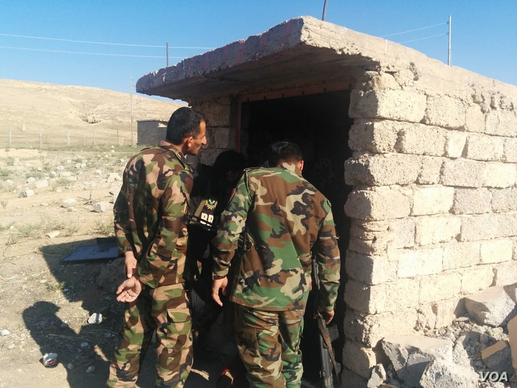 Peshmerga soldiers examine a tunnel build by Islamic State militants, one of the ways the group managed to hold villages for more than two years in Tarjala in the Kurdish region of northern Iraq, Oct. 29, 2016. (H. Murdock/VOA)