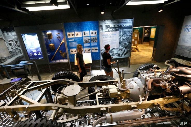 """Workers walk past a mock-up of an assembly line manufacturing army jeeps as part of the permanent exhibit """"Salute to the Home Front"""" at the National World War II Museum."""