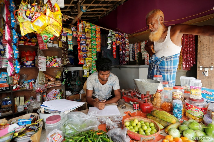 FILE - A man from the Rohingya community fills out an identification form provided by local police inside his shop at a camp in New Delhi, Oct. 4, 2018.