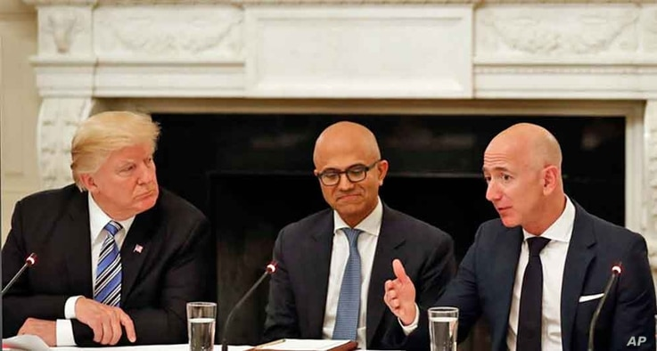 President Donald Trump, left, and Satya Nadella, Chief Executive Officer of Microsoft, center, listen as Jeff Bezos, Chief Executive Officer of Amazon, speaks during an American Technology Council roundtable in the State Dinning Room of the White Hou...
