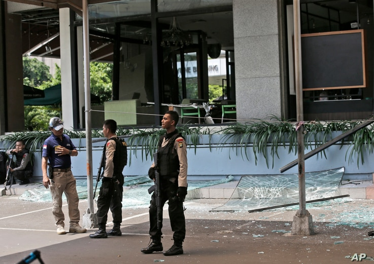 Police officers stand guard outside a damaged Starbucks cafe after an attack in Jakarta, Indonesia Thursday, Jan. 14, 2016.