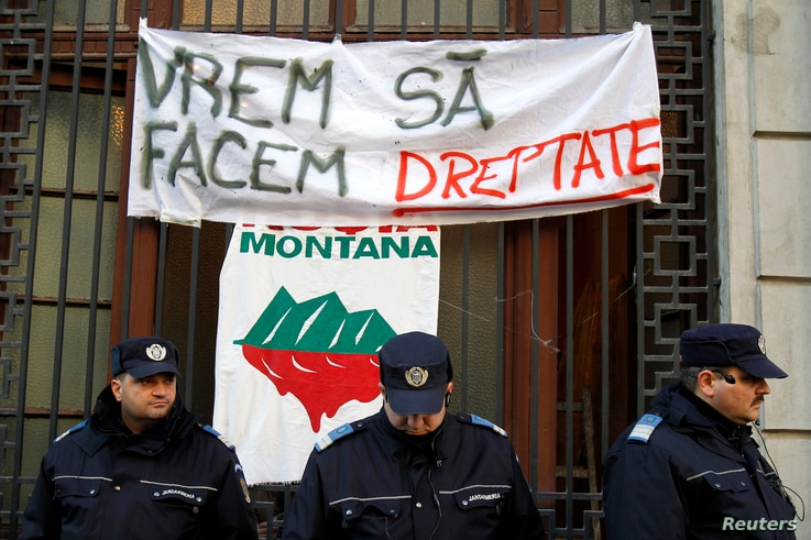 Banners are seen behind gendarmes after environmentalist activists occupied the People Advocate's headquarters in Bucharest, Dec. 10, 2013. They are  protesting against a Canadian company's project to set up Europe's biggest open cast gold mine in R...