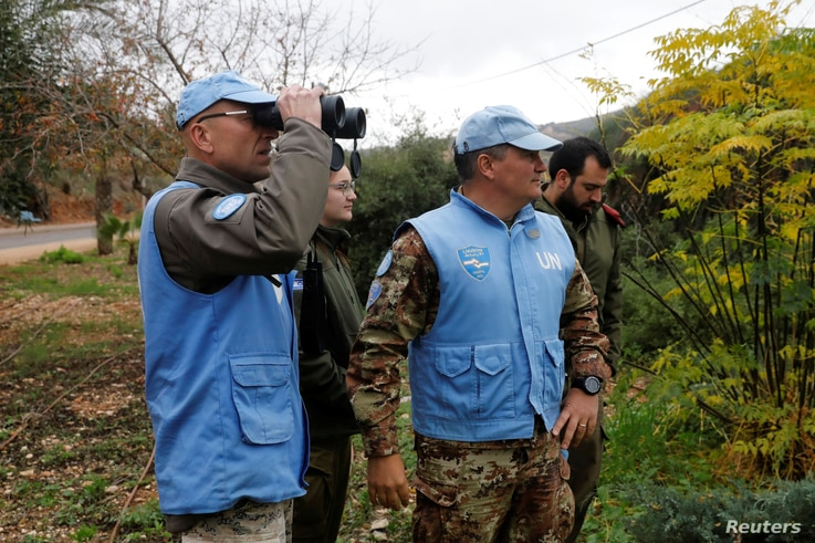 "U.N. peacekeepers and Israeli soldiers look towards the border with Lebanon the morning after the Israeli military said it had launched an operation to ""expose and thwart"" cross-border attack tunnels from Lebanon, in Israel's northernmost town Metula..."