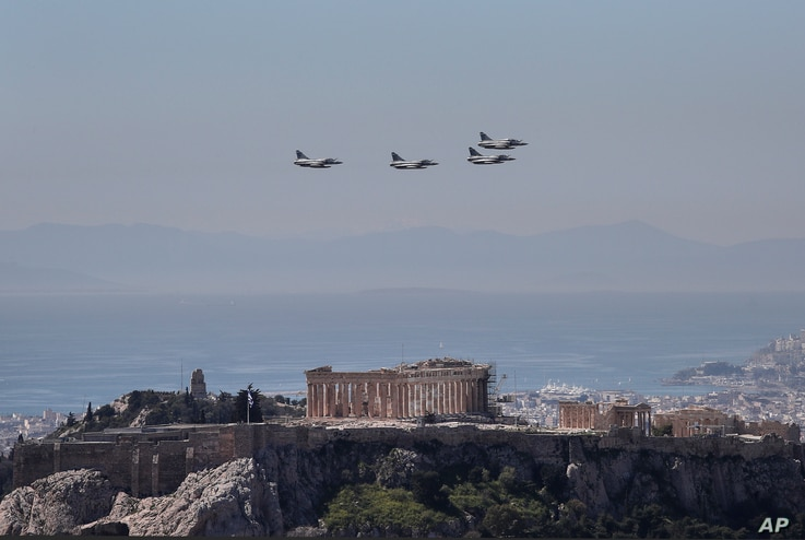 A formation of Greek fighter jets flies over the temple of the Parthenon, on the ancient Acropolis hill during a military parade in Athens March 25, 2017.