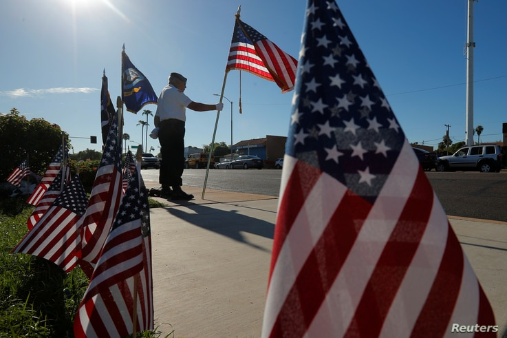 Honor guard member and Vietnam War veteran David Carrasco stands at a makeshift memorial outside the funeral home where the body of the late U.S. Senator John McCain rests in Phoenix, Arizona, Aug. 28, 2018.