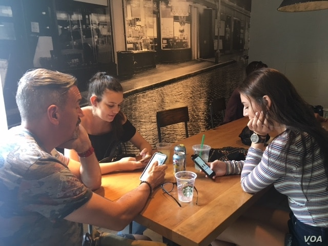 A father and his two daughters take a break from sightseeing at a Starbucks in Washington D.C. (VOA/CMaddux)