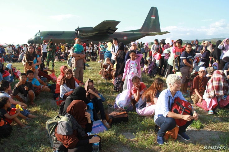 Local residents affected by the earthquake and tsunami wait to be airlifted out by military planes at Mutiara Sis Al Jufri Airport in Palu, Central Sulawesi, Indonesia, Sept. 30, 2018, in this photo taken by Antara Foto.