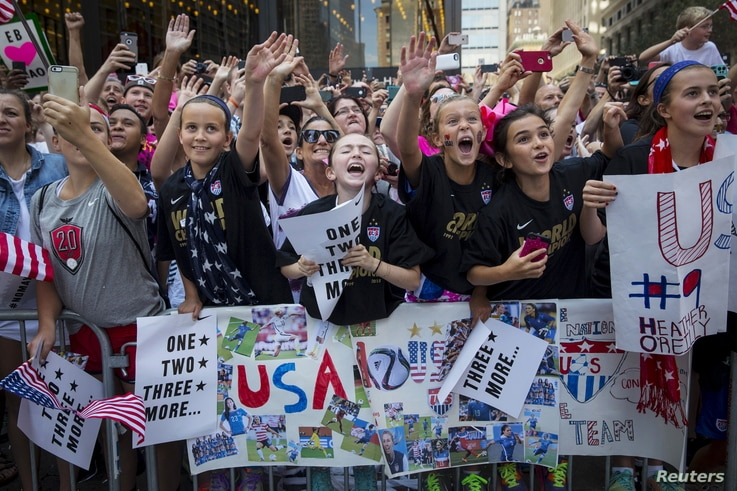Fans of the U.S. women's soccer team cheer during the ticker tape parade to celebrate their World Cup final win over Japan on Sunday, in New York, July 10, 2015.