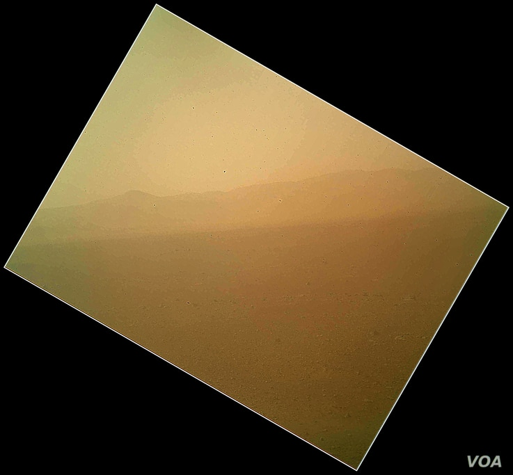 The image shows the first color view of the north wall and rim of Gale Crater where Curiosity landed Sunday night. The picture was taken by the rover's camera at the end of its stowed robotic arm and appears fuzzy because of dust on the camera's cove...