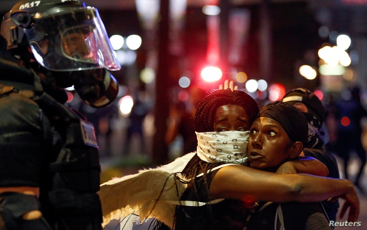 Two women embrace while looking at a police officer in uptown Charlotte, NC during a protest of the police shooting of Keith Scott, in Charlotte, North Carolina, U.S. Sept. 21, 2016.